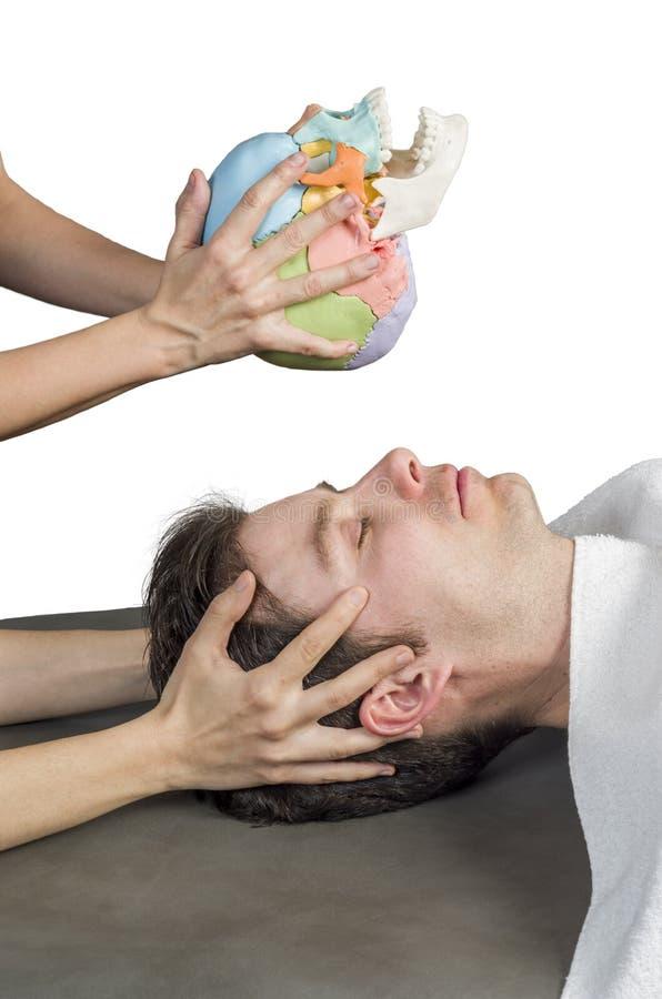 Physiotherapeut, der eine kraniale sakrale Therapie tut stockfoto