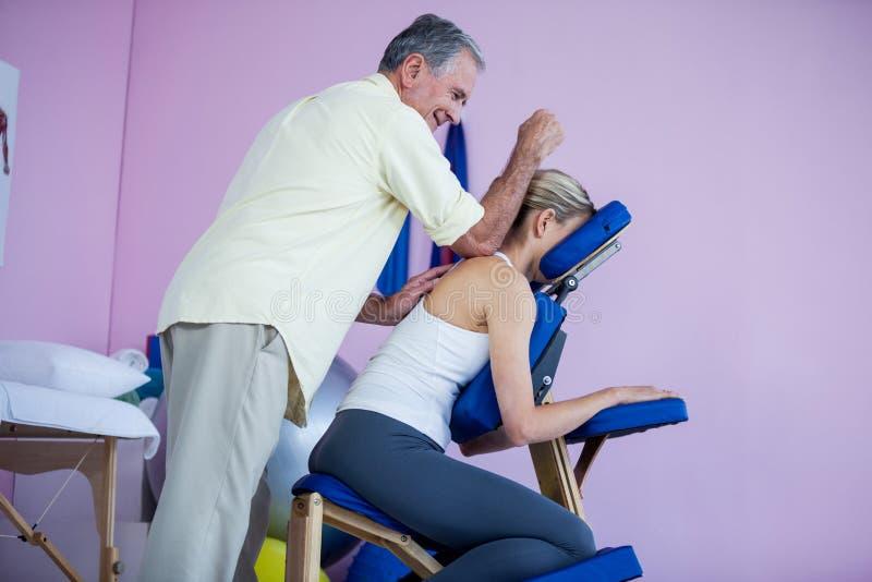 Physiotherapeut, der einem Patienten Rückenmassage gibt stockfotografie