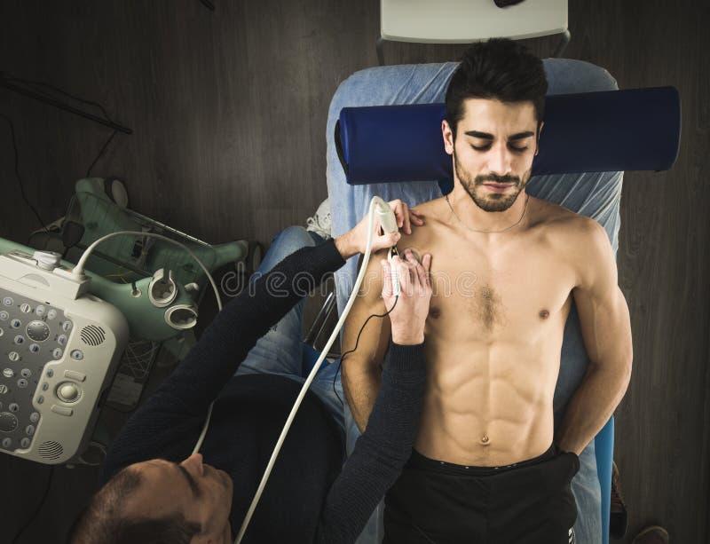 Physiotherapeut, der einen Patienten mit einem Ultraschallscan überprüft Physiotherapie und Rehabilitation lizenzfreies stockfoto