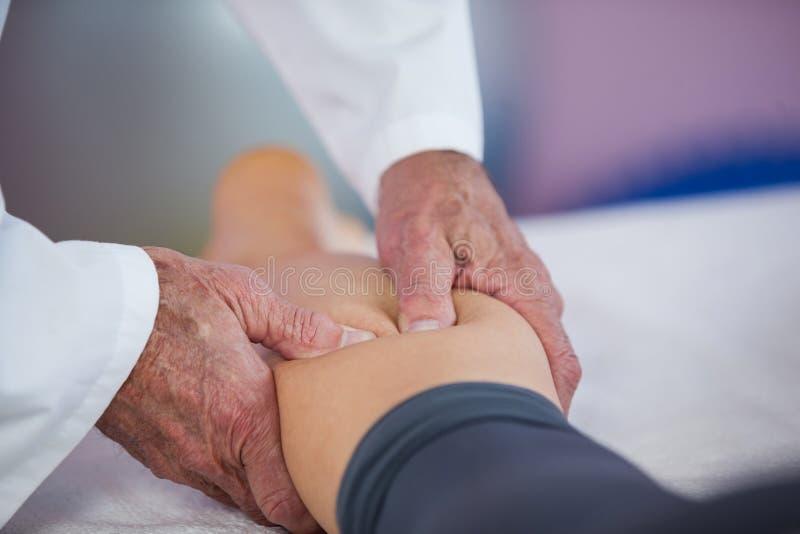 Physiotherapeut, der einer Frau Beinmassage gibt stockbild