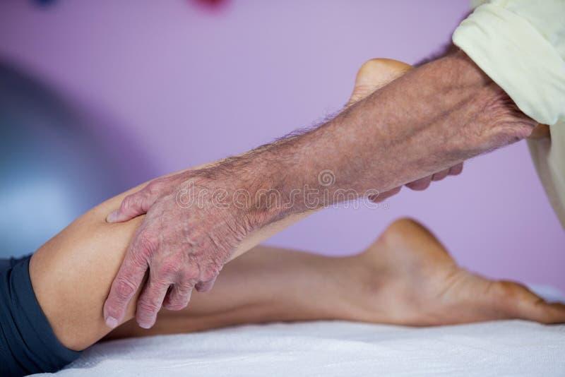 Physiotherapeut, der einer Frau Beinmassage gibt lizenzfreie stockbilder