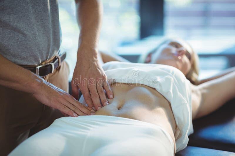 Physiotherapeut, der einer Frau Magenmassage gibt lizenzfreie stockfotografie
