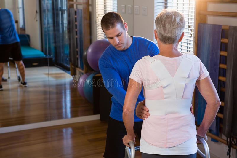 Physiotherapeut, der Patienten unterstützt, um mit gehendem Rahmen zu gehen lizenzfreies stockbild