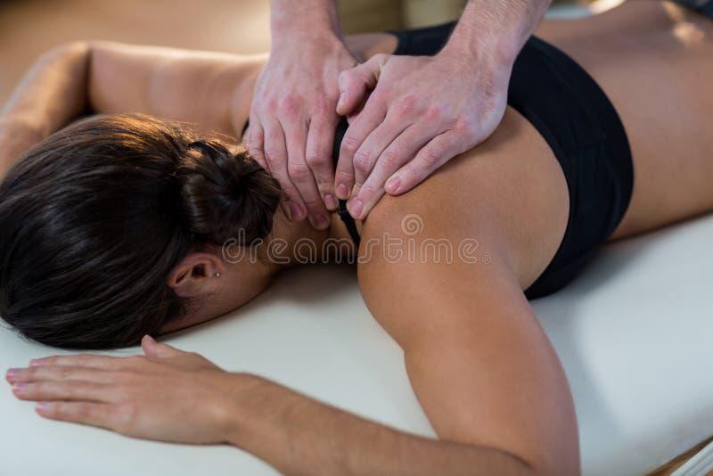 Physiotherapeut, der Physiotherapie zum Hals eines weiblichen Patienten gibt stockfoto