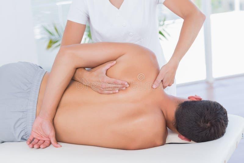 Physiotherapeut, der Rückenmassage ihren Patienten antut lizenzfreie stockbilder