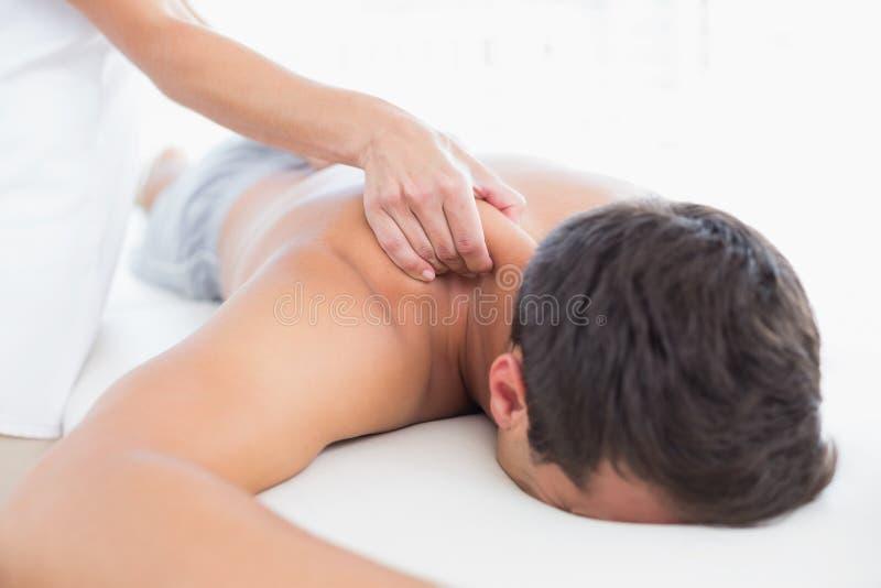 Physiotherapeut, der Schultermassage ihren Patienten antut stockfoto