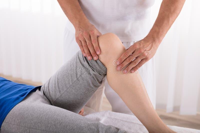 Physiotherapeut Giving Knee Exercise zur Frau lizenzfreies stockfoto