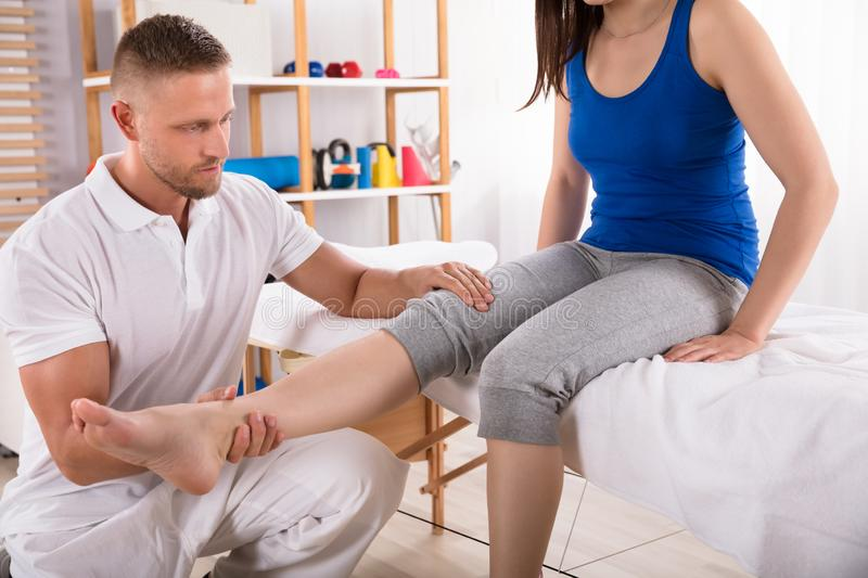 Physiotherapeut Giving Leg Massage zur Frau lizenzfreie stockfotos