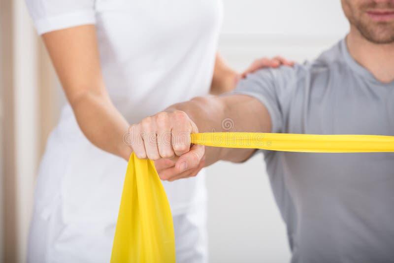 Physiotherapeut Giving Man ein Training mit Übungs-Band lizenzfreie stockfotografie