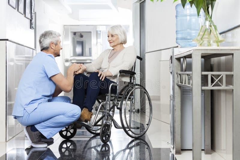 Physiotherapeut Holding Senior Patients Hand auf Rollstuhl lizenzfreie stockfotos