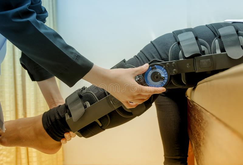 Physiotherapeut justieren Kniestützen auf geduldigem ` s Bein, Rehabilitat lizenzfreies stockbild
