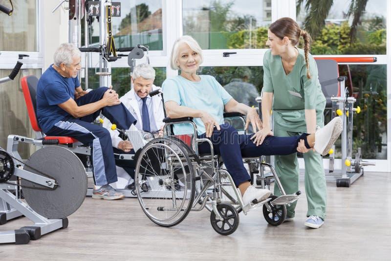 Physiotherapeuten, die ältere Patienten zur Übung am Rehabilitations-Cer führen stockbild