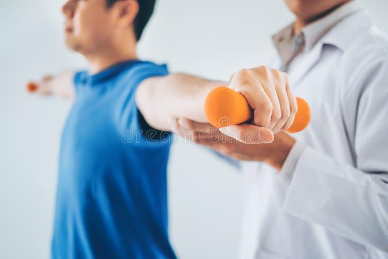 Physiotherapeutenmann, der Übung mit Dummkopfbehandlung über Arm und Schulter Athlet männlicher geduldiger Physiotherapie gibt lizenzfreie stockfotografie