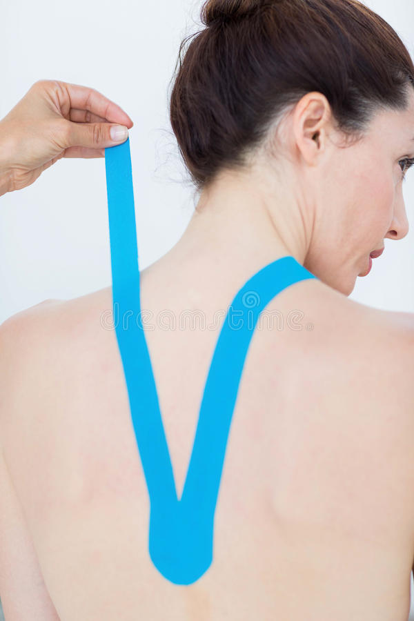 Physiotherapist applying blue kinesio tape to patients back. In medical office royalty free stock photos
