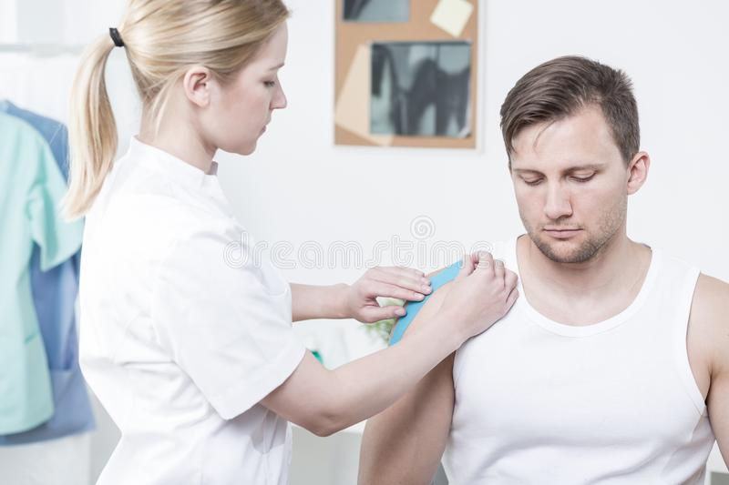 Physiotherapist applying kinesiology tape. For painful shoulder royalty free stock images