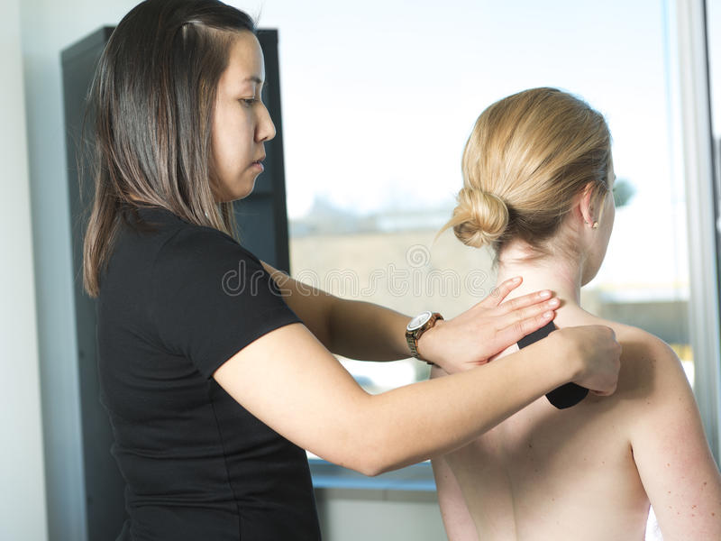 Physiotherapist applying kinesiology tape for painful shoulder. A Physiotherapist applying kinesiology tape for painful shoulder royalty free stock photos