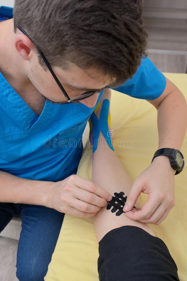 Physiotherapist applying kinesiology tapes royalty free stock images