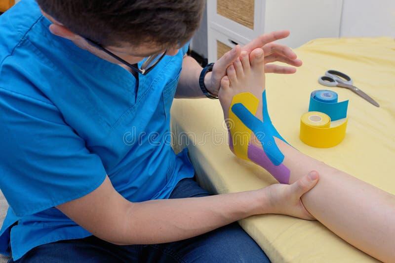 Physiotherapist applying kinesiology tapes on leg stock photos