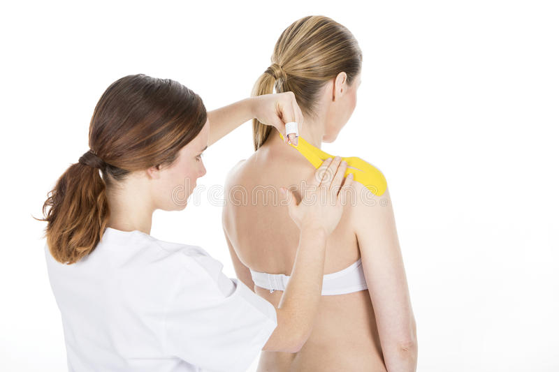 Physiotherapist applying tapes. On a shoulder royalty free stock photos