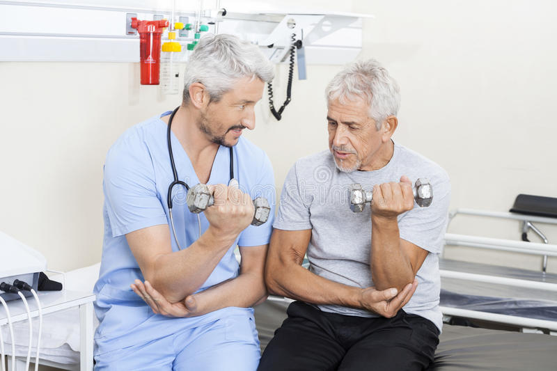 Physiotherapist Assisting Senior Man In Lifting Dumbbells royalty free stock image