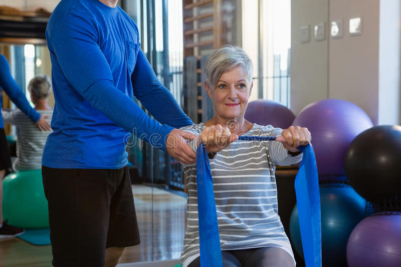 Physiotherapist assisting senior woman in performing stretching exercise with resistance band. Physiotherapist assisting senior women in performing stretching stock photography