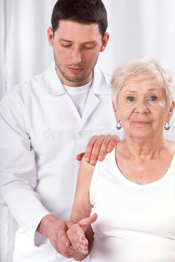 Physiotherapist checking arm motor abilities. Physiotherapist checking elderly patient's arm motor abilities royalty free stock photography