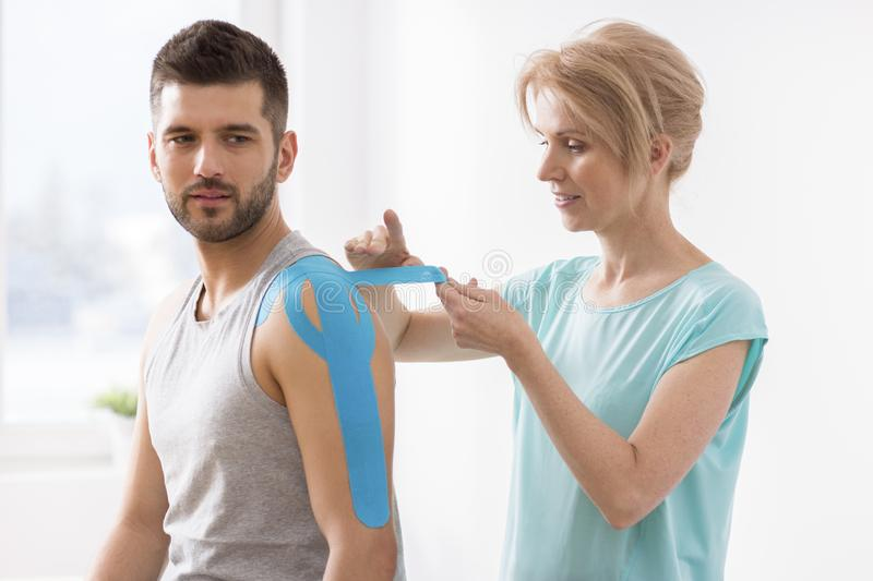 Physiotherapist covering selected fragments of young man`s body with special structure patches during kinesiotaping therapy. Physiotherapist covering selected royalty free stock photo