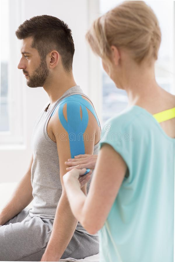 Physiotherapist covering selected fragments of young man`s body with special structure patches during kinesiotaping therapy. Physiotherapist covering selected royalty free stock photography