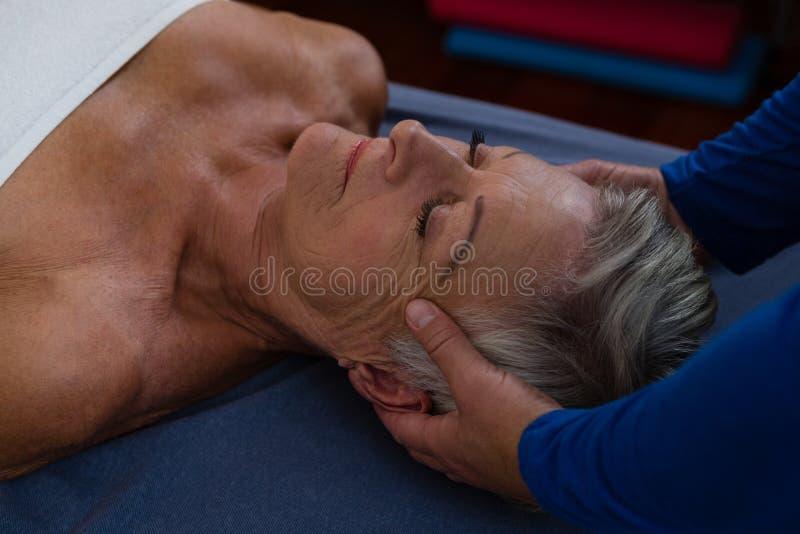 Physiotherapist daje kierowniczemu masażowi starsza kobieta obrazy royalty free