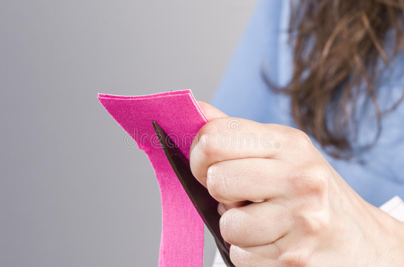 Physiotherapist / doctor is cutting pink kinesiotape stock photography