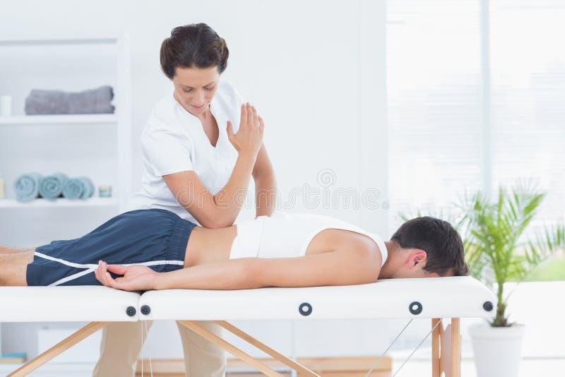Physiotherapist doing back massage stock photos