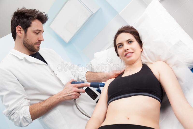 A physiotherapist doing a eswt treatment to a woman. A dark hair women having a extra corporeal shock wave therapy for a shoulder pain with a physiotherapist royalty free stock photography