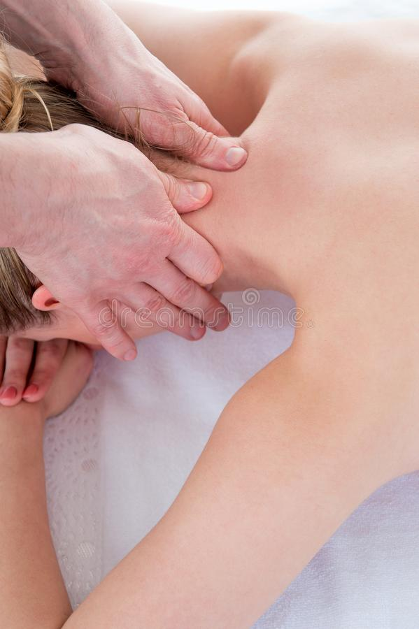 Physiotherapist doing neck massage in medical office stock photo