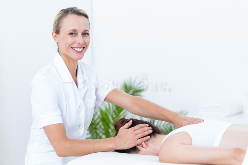 Physiotherapist doing neck massage stock images