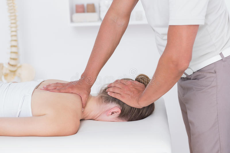 Physiotherapist doing neck massage. To his patient in medical office royalty free stock photos