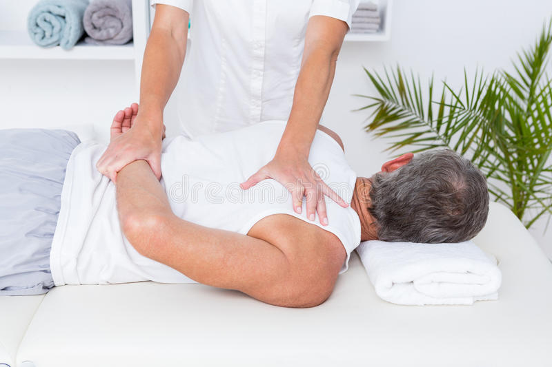 Physiotherapist doing shoulder massage to her patient royalty free stock images