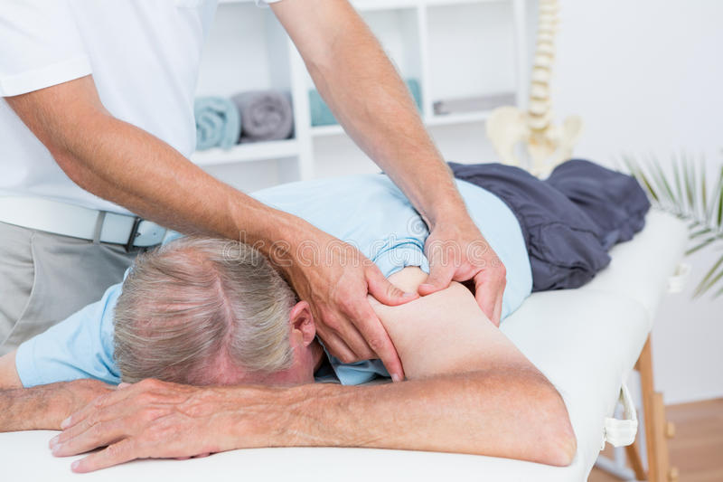 Physiotherapist doing shoulder massage to his patient stock image