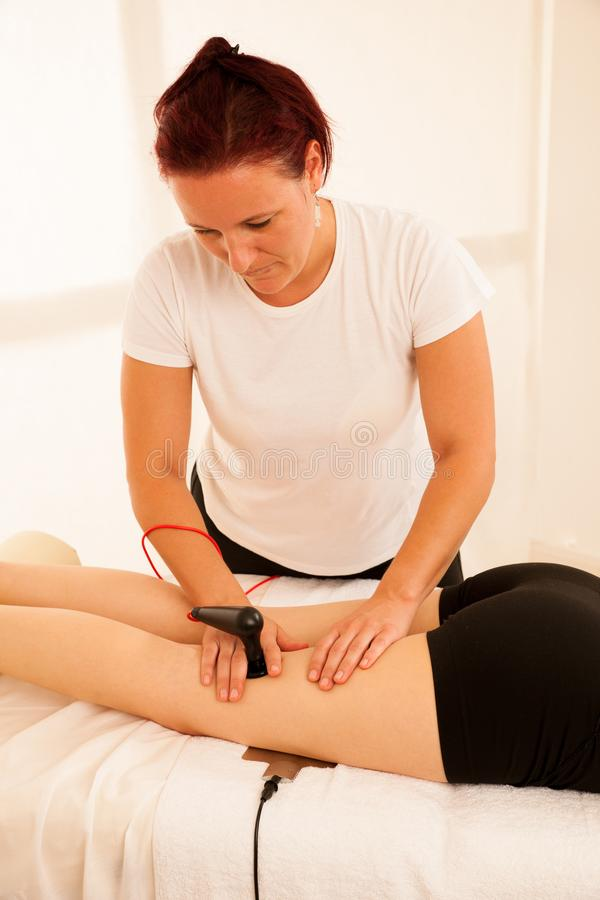Physiotherapist doing Tecar therapy alterantive treatment on a w stock image