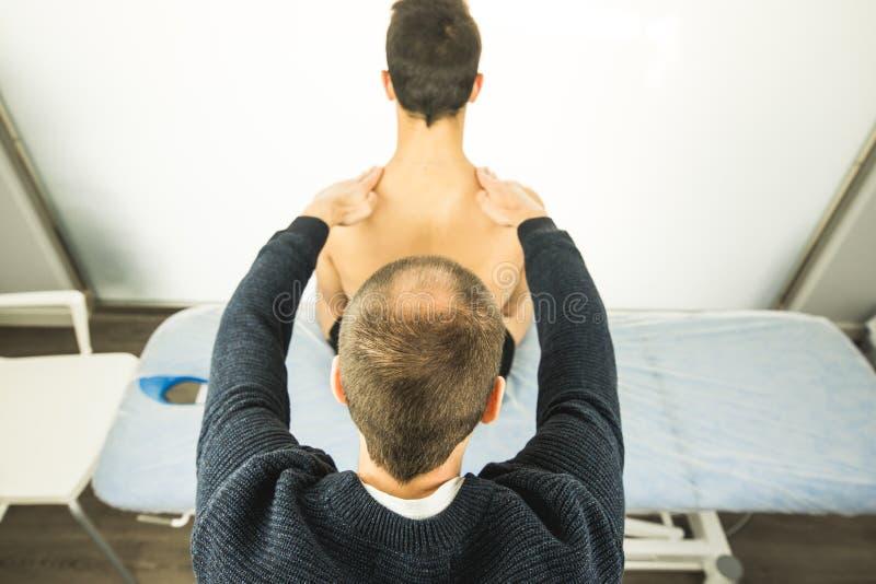 Physiotherapist egzamininuje młodego człowieka plecy Fizjoterapii pojęcie obrazy royalty free