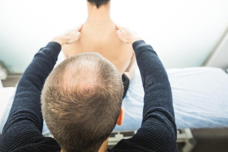 Physiotherapist egzamininuje młodego człowieka plecy Fizjoterapii pojęcie zdjęcia stock
