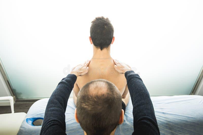 Physiotherapist egzamininuje młodego człowieka plecy Fizjoterapii pojęcie obraz royalty free