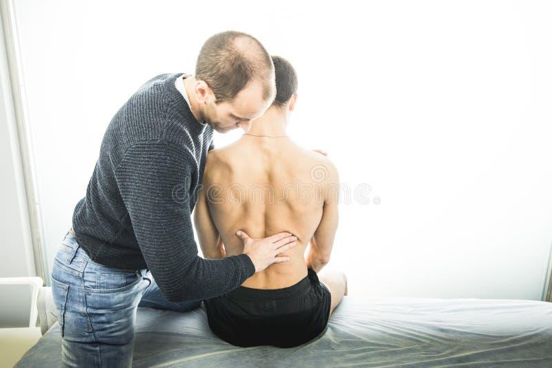 Physiotherapist egzamininuje młodego człowieka plecy Fizjoterapii pojęcie zdjęcie royalty free