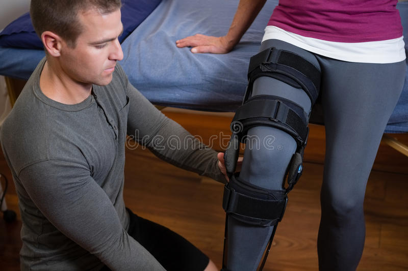 Physiotherapist examining his patients knee royalty free stock photos
