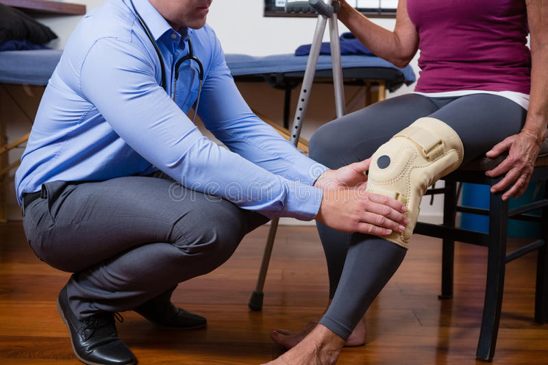 Physiotherapist examining his patients knee stock photo