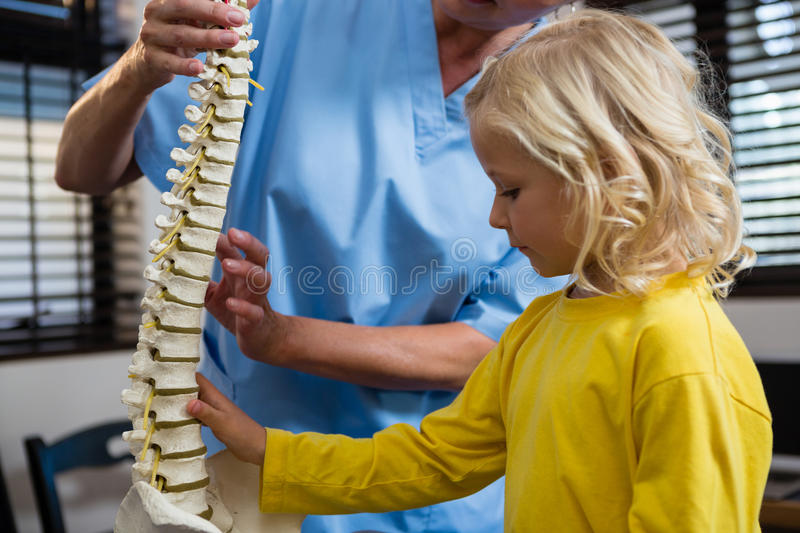 Physiotherapist explaining the spine to girl patient royalty free stock photos