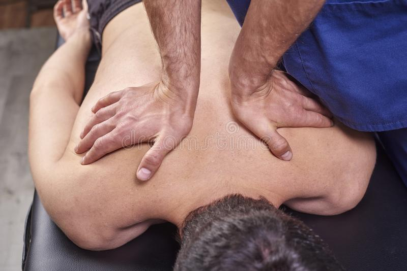 Physiotherapist giving a back massage. Chiropractic, osteopathy, manual therapy, acupressure royalty free stock images