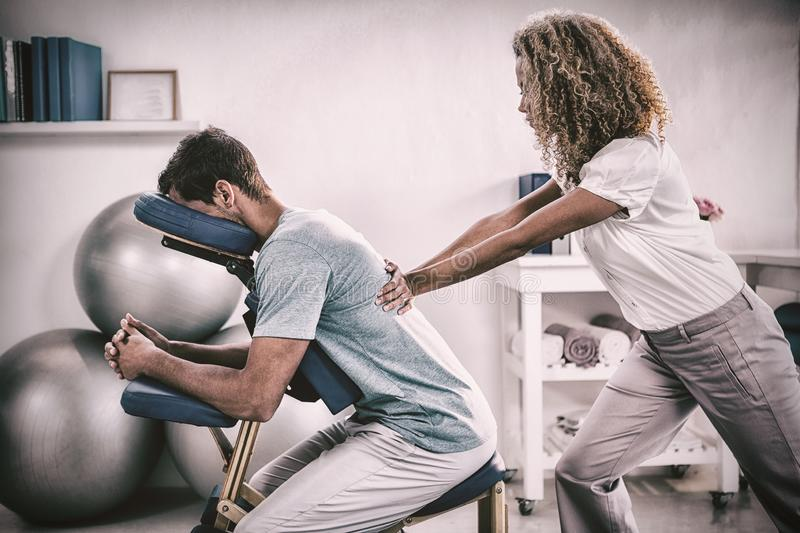 Physiotherapist giving back massage to a patient stock photography