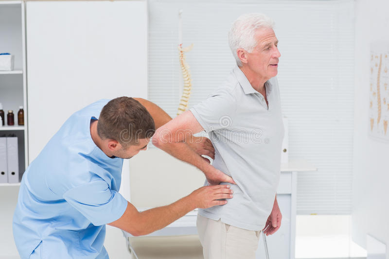 Physiotherapist giving back massage to senior man stock images