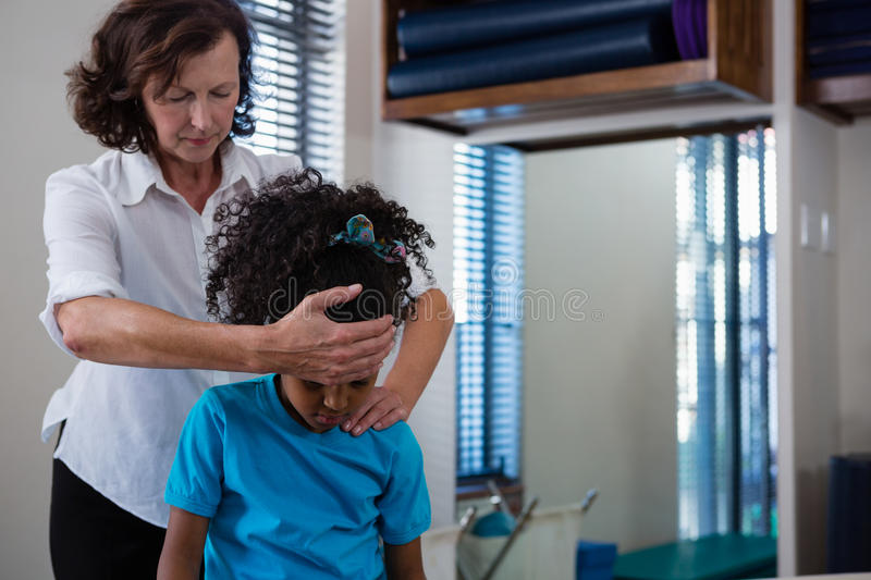 Physiotherapist giving neck massage to girl patient. In clinic royalty free stock photos
