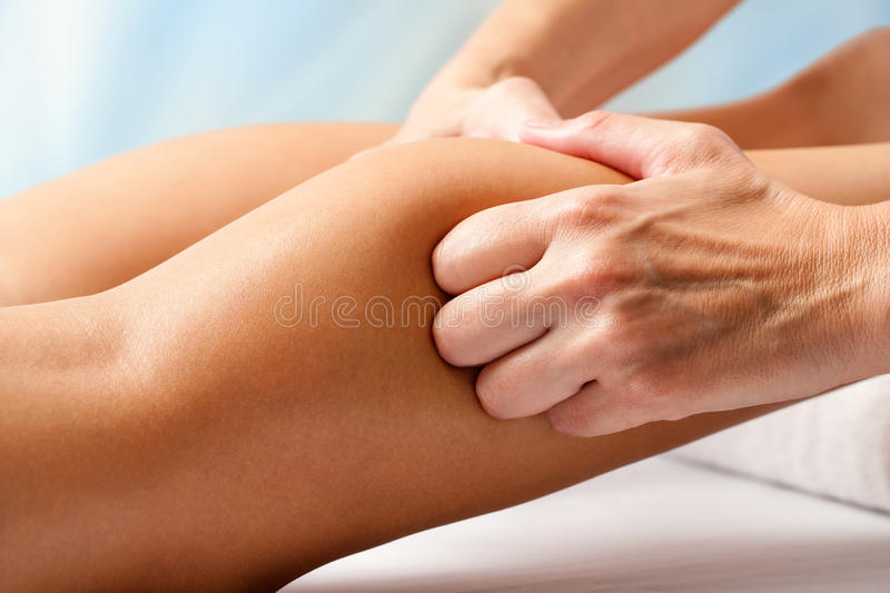 Physiotherapist hands massaging calf muscle. Macro close up of Physiotherapist hands massaging female calf muscle royalty free stock photography